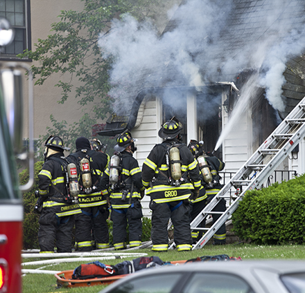 Firefighters responding to a house on fire.